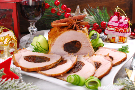 plum: partly sliced roasted pork loin in honey glaze stuffed with plum for christmas dinner