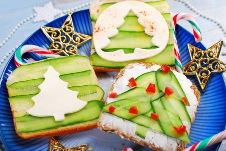 comida de navidad: tres sándwiches de la forma del árbol de Navidad con rodajas de pepino y queso blanco para el desayuno festivo Foto de archivo