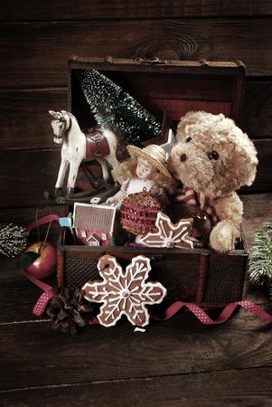 osos navideños: juguetes de Navidad de la vendimia como muñeca, oso de peluche, caballo de oscilación y las decoraciones en el viejo cofre del tesoro en el fondo de madera Foto de archivo
