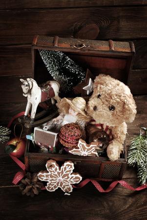 infancia: juguetes de Navidad de la vendimia como muñeca, oso de peluche, caballo de oscilación y las decoraciones en el viejo cofre del tesoro en el fondo de madera Foto de archivo