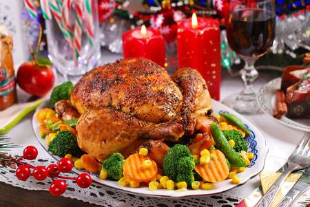 légumes verts: poulet rôti entier avec des légumes colorés sur la table de Noël