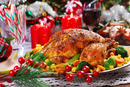 baked: roasted whole chicken with colorful vegetables on christmas table Stock Photo