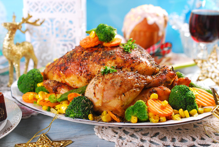 baked meat: roasted whole chicken with  broccoli,carrot,corn and green peas on christmas table