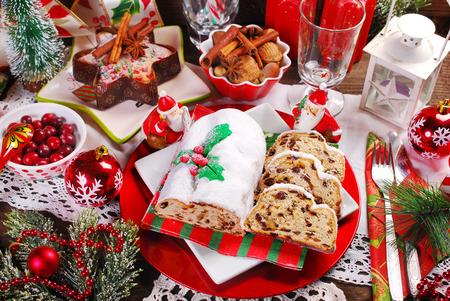 Kerstmis stollen cake gedeeltelijk gesneden met gedroogde vruchten en marsepein op feestelijke tafel