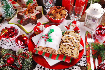 christmas stollen cake partly sliced with dried fruits and marzipan on festive table