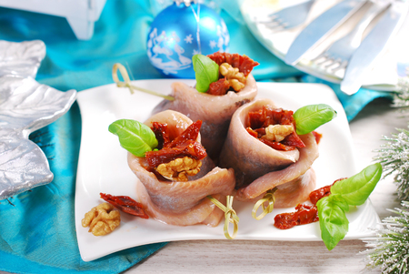 comida de navidad: appetizer of spicy herring rolls with dried tomato and walnuts on christmas table Foto de archivo