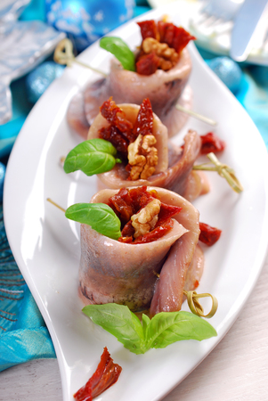dried fish: appetizer of spicy herring rolls with dried tomato and walnuts on christmas table Stock Photo