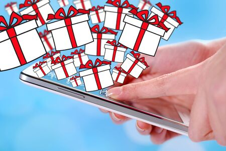 easy: buying christmas presents to a smartphone with drawn gift boxes on blue background Stock Photo