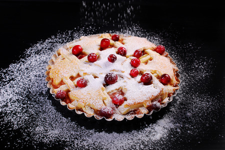 powdered sugar: apple pie with cranberry and powdered sugar on black table