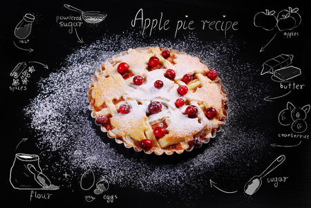 fruitcakes: apple pie with cranberry and powdered sugar and drawing recipe on black table