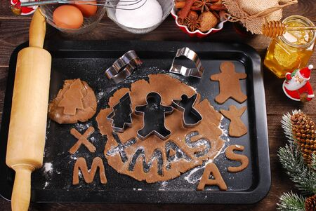 plastic christmas tree: christmas gingerbread dough and cookie cutters on black tray with ingredients and utensils