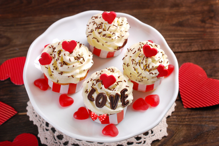 four month: four valentine cupcakes with whipped cream ,red hearts and chocolate letters LOVE  on wooden  background Stock Photo