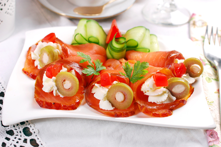 salmon appetizer rolled in cone shape with cream cheese and green olives on festive table