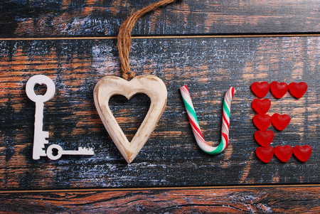 feelings and emotions: the word LOVE made of wooden keys,heart,cane candy and red heart shaped candies on shabby background