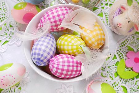 decoracion mesas: huevos de pascua de colores y plumas blancas en un tazón Foto de archivo