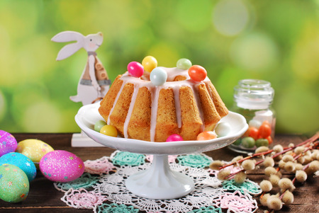 easter almond ring cake with icing and colorful candy eggs on the top on wooden table