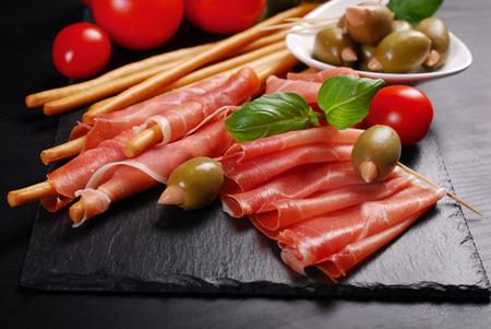 breadstick: italian grissini stick bread with prosciutto ham and olives on black board