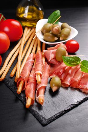 grissini: italian grissini stick bread with prosciutto ham and olives on black board