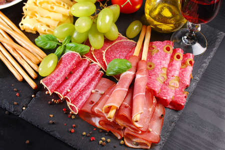 delicatessen: italian grissini stick bread with prosciutto ham  on black board with appetizers