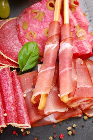 breadstick: italian grissini stick bread with prosciutto ham  on black board with appetizers