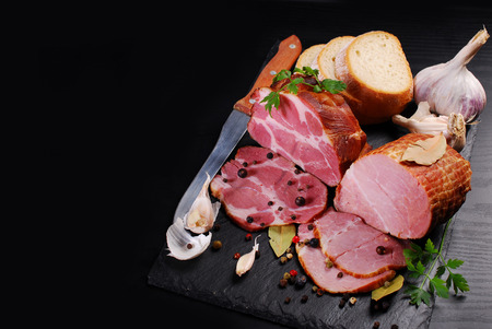 pieces of delicious homemade smoked pork ham with spices and bread on black background and space for own text