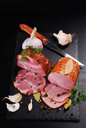 pieces of delicious homemade smoked pork ham with spices on black background
