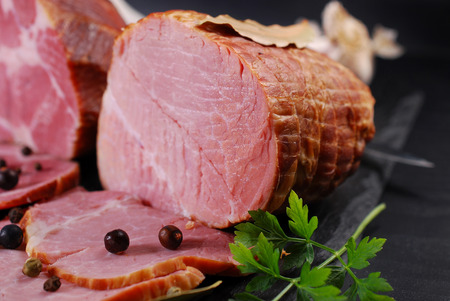 cured ham: pieces of delicious homemade smoked pork ham with spices on black background