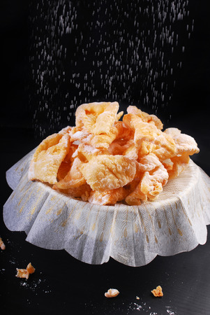 icing sugar: traditional in Poland for carnival party deep-fried pastry -faworki- with falling icing sugar on black background Stock Photo