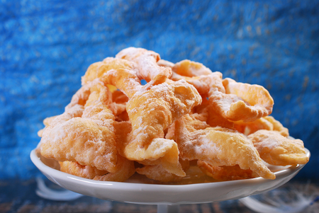 brushwood: traditional in Poland for carnival deep-fried pastry with icing sugar -faworki- on blue background