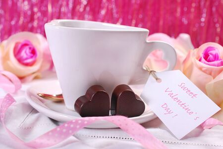 cafe bombon: in heart shaped coffee cup with greetings on paper tag and two chocolates for romantic valentines day
