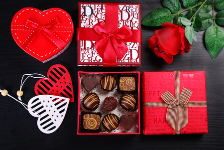 red gift boxes with chocolate pralines and rose on black background for valentines day Archivio Fotografico