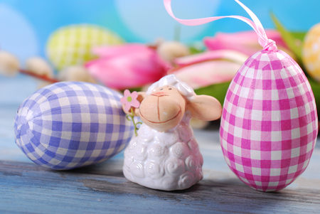 pasen schaap: easter greeting card with cute lamb figurine and eggs on blue wooden table