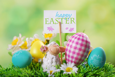 easter greeting card with cute lamb figurine and egg on the grass