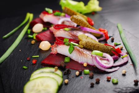 aperitivo de arenque con trozos de remolacha, pepinillo, cebolla roja y cebolleta en tabla de pizarra negro
