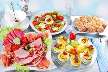 traditional easter breakfast with ham and cured meat platter,salad,stuffed eggs and white sausage with onion