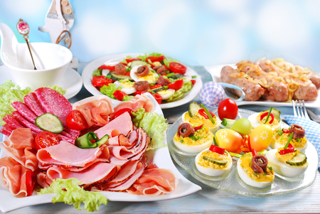 traditional easter breakfast with stuffed eggs,ham and cured meat platter,salad and white sausage with onion