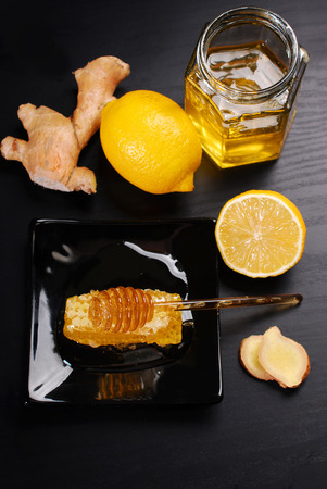 honey comb: golden honey with comb ,fresh lemons and ginger on black background Stock Photo