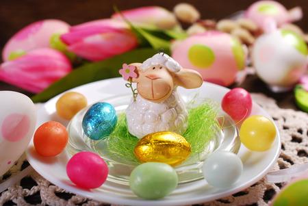 pasen schaap: tafeldecoratie Pasen met leuke lam beeldje en snoep eieren op een witte plaat
