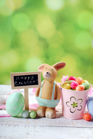 funny easter: easter card with funny  clay rabbit ,eggs and chalkboard with greetings text on green spring background Stock Photo