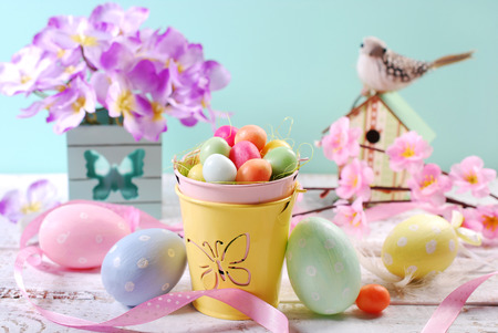 easter pastel colors decoration with candy eggs in small bucket,painted eggs,bird and flowers on old wooden table