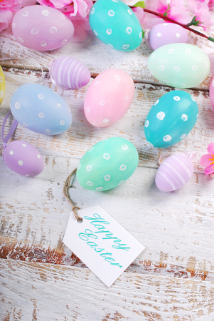wooden color: easter background with pastel color eggs and paper tag with greetings text on old wooden table