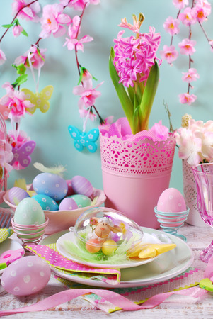 setting: beautiful easter table decoration with painted eggs and spring flowers in pastel colors