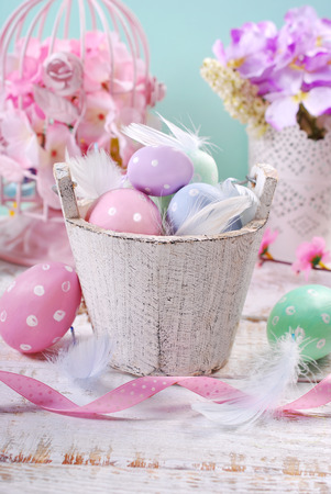 wooden color: old wooden bucket with pastel color easter eggs and feathers Stock Photo