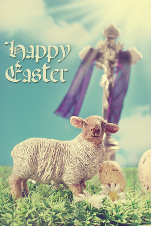 vintage greeting card with Jesus Christ on the cross and lamb figurine against blue sky as a symbol of Easter