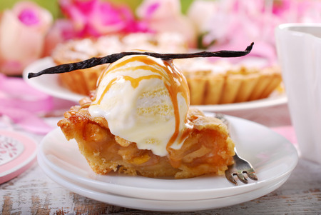slice of homemade apple pie served with vanilla ice cream and caramel