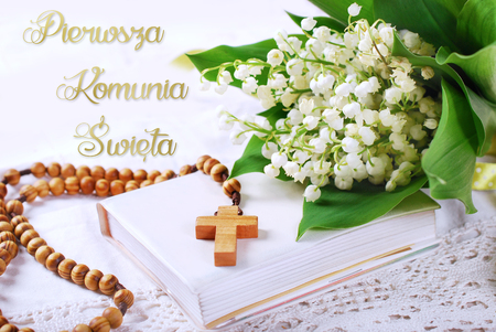 the first holy communion with wooden rosary,prayer  book and bunch of lily of the valley-polish language version