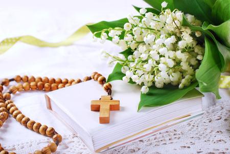 de eerste heilige communie met houten rozenkrans, gebed boek en bos van lelietje-van-dalen Stockfoto