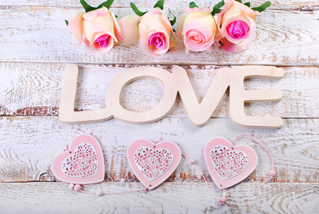 romantic love: romantic love background with  word love,hearts and roses on white wooden planks