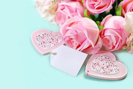 Fond d'amour romantique en couleurs pastel avec un tas de roses roses, coeurs et étiquette en papier pour le propre texte