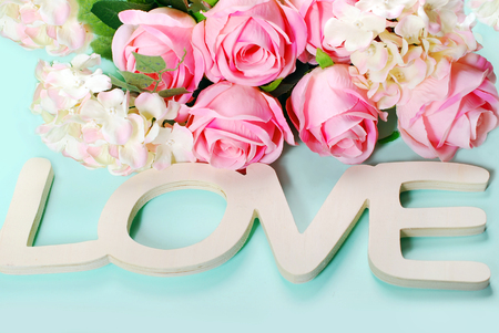romantic love: romantic love background in pastel colors with wooden word love and roses Stock Photo